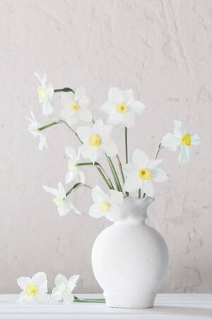 white narcissus in vase on wooden table