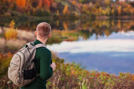 young tourist with  backpack near  autumn lake