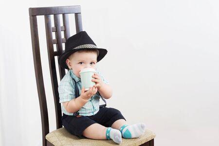 petit monsieur au chapeau est assis sur une chaise Banque d'images