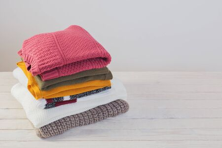 stack of sweaters on  white wooden table