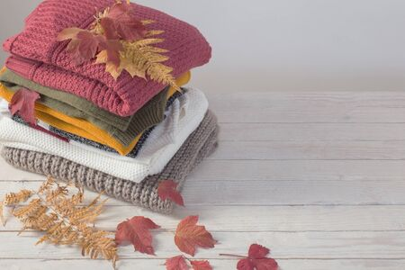 stack of sweaters with autumn leaves  on  white wooden table