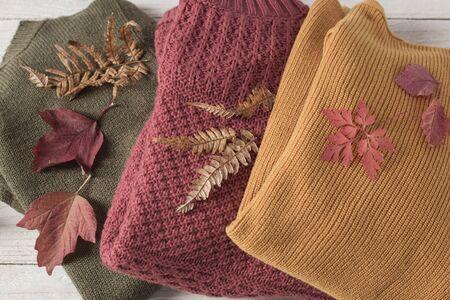 stos swetrów z jesiennymi liśćmi na białym drewnianym stole Zdjęcie Seryjne