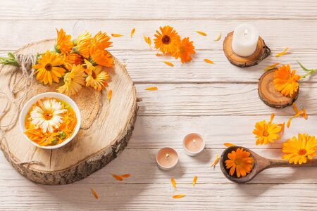 Medicinal flowers of calendula with burning candles  on white wooden background Zdjęcie Seryjne