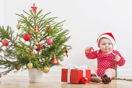 funny baby with little Christmas fir at home 写真素材