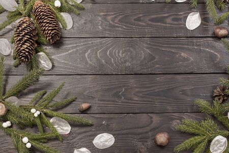 Christmas fir branches and decorations on dark wooden background Фото со стока