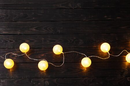 Christmas golden lights on dark wooden background Stock fotó