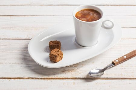cup of coffee with chocolate candy on white old wooden table