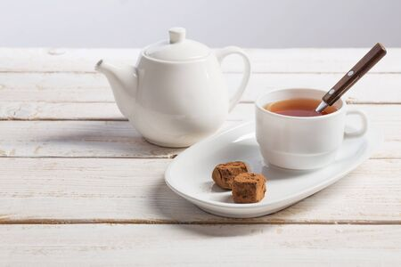 cup of tea with chocolate candy on wooden table