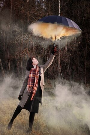 teenager girl with black umbrella and smoke   in autumn field Standard-Bild