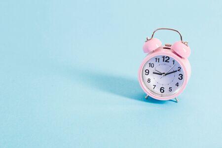 Despertador rosa sobre fondo azul. Foto de archivo