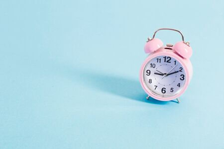 pink alarm clock on blue background