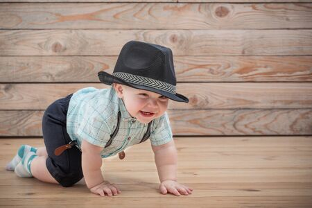 baby in black hat, shirt and suspenders shorts  on wooden background
