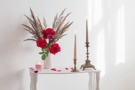 white interior with bouquet of roses and burning candles Banque d'images - 133510890