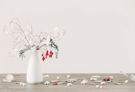 bouquet with lunaria and red berries in white vase on wooden table Standard-Bild - 134130768
