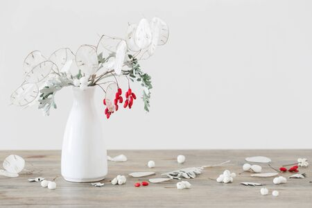 bouquet with lunaria and red berries in white vase on wooden table Standard-Bild - 134130769