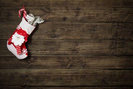 Weihnachtsstrumpf mit Geschenken, die auf dunklem altem Holzhintergrund hängen Standard-Bild