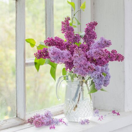 bouquet of lilacs in a glass jug on old white windowsill