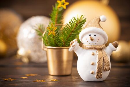 Christmas golden decorations and snowman on dark wooden background