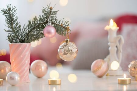 Christmas decorations with burning candles in pink and gold colors