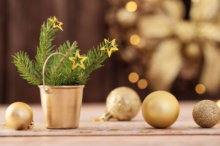 Christmas golden balls, fir branches  and wreath on dark wooden background Stock Photo