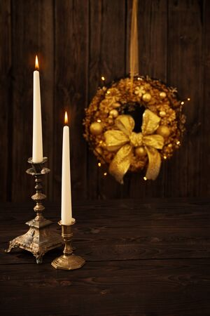 two candles in candlesticks on background Christmas wreath on dark wooden background
