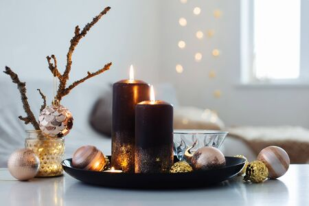 black burning candles with Christmas balls in white interior