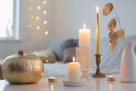 home decor with golden pumpkin and burning candles Stock Photo