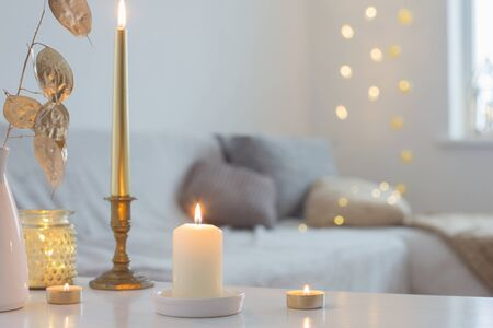 burning candles on table in white interior