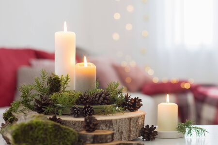 Composition of candles on  white table against the background of sofa at home Stock Photo