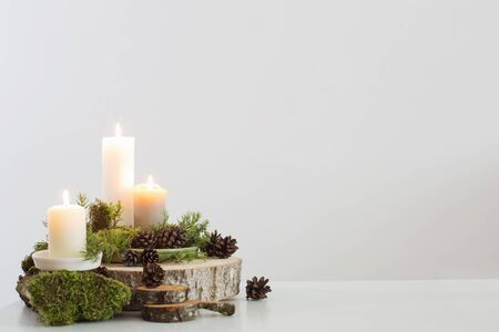 burning candles on saw with cones and branches on white background