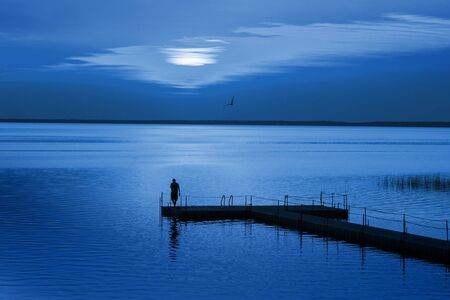 Man on pontoon pier in blue night. Color of the year 2020 Classic Blue