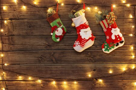 Christmas stocking with gifts hanging on dark old wooden background