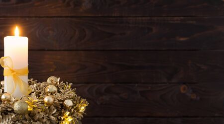 Christmas golden wreath with  burning candle on dark wooden background