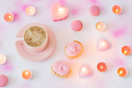cup of coffee with burning candles on pink painted paper background