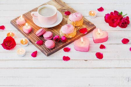cup of coffee with cakes, candles and roses on white wooden background