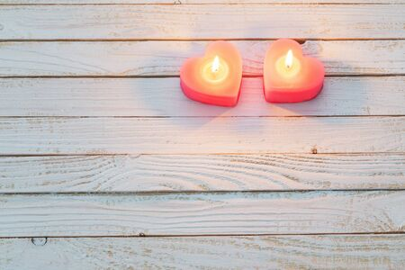 pink burning candles on white wooden background