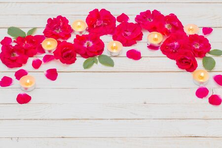 red roses and burning candles on wooden white background