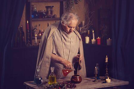 Un vieux moine alchimiste prépare une potion magique Banque d'images