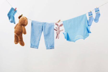 baby clothes hanging on rope on white background