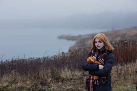 Sad blonde teenager  girl hugging  teddy bear by foggy  lake.  Concept of adolescence and adolescent problems. Standard-Bild