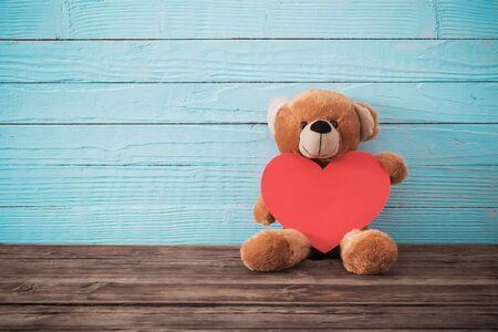 Teddybär mit rotem Herzen auf altem hölzernem Hintergrund. Valentinstag Konzept