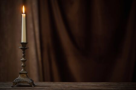 antique candlestick with burning candle on old wooden table on background brown velvet curtain