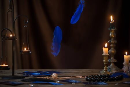 blue falling bird feathers over wooden table with fortunetelling cards and antique candlesticks