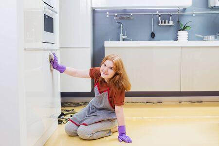 girl in purple gloves washes cupboard in kitchen