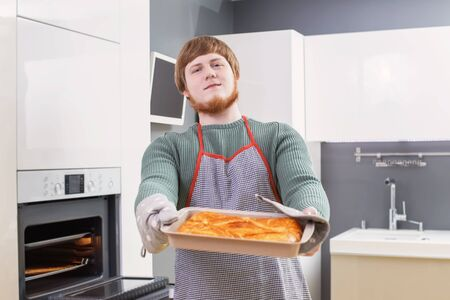 young man with red beard making pie on white modern kitchen