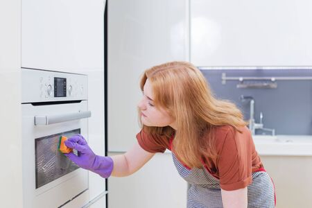 girl in purple gloves sponges oven in modern kitchen