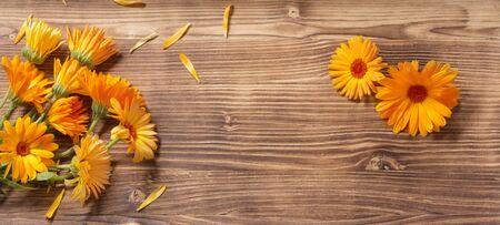calendula flowers on dark wooden background