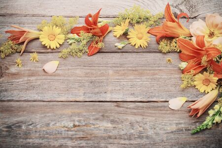 yellow and orange flowers on old wooden background