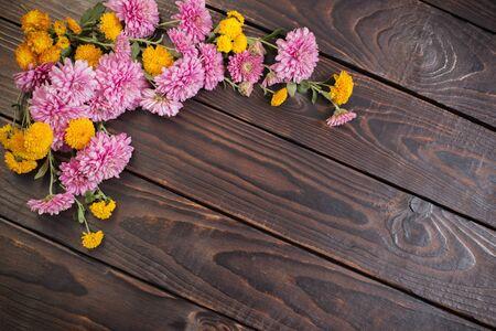 pink and orange chrysanthemums on dark wooden background