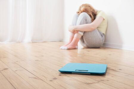 sad teenager girl with scale on wooden floor